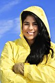 Portrait of beautiful smiling brunette girl wearing yellow raincoat against blue sky