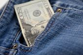 stock photo of twenty dollars  - A twenty dollar bill sticking out the front pocket of denim blue jeans