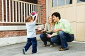 image of bounce house  - Happy young family playing soccer with toddler on driveway - JPG