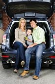 Happy young family sitting at back of car