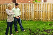 Young couple worried about growing lawn in backyard of new home