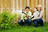 Happy family in backyard watering plant with hose