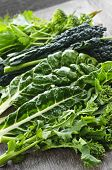 stock photo of roughage  - Dark green leafy fresh vegetables on cutting board - JPG