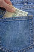 pic of twenty dollar bill  - A person pulling a twenty dollar bill out of a denim blue jean back pocket - JPG