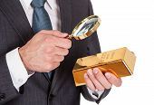 Businessman Looking At Gold Bar Through Loupe