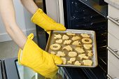 Taking fresh baked shortbread cookies from oven in kitchen