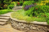 Natural stone landscaping in home garden with stairs and retaining walls
