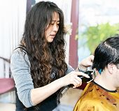 Hairdresser cutting hair in her salon with trimmer