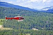 Red rescue helicopter flying emergency mission in mountains, Alberta Canada