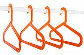 Orange Hangers On A Rod Isolated On White