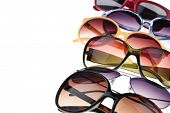 Assorted styles of tinted sunglasses on white background