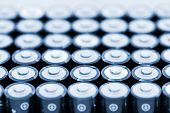 Tops of many AA batteries in closeup