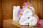 White rolled up spa towels with body care products