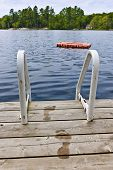 Wet footprints on dock with ladder and diving platform at lake in Ontario Canada