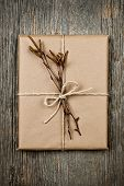 Simple gift package in brown paper decorated with birth branches on rustic wood background