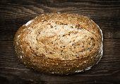 Artisan loaf of freshly baked multigrain bread on wooden background