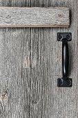 Distressed rustic barn wood door with handle as textured background