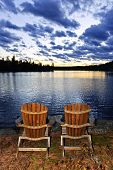 Landscape with adirondack chairs on shore of relaxing lake at sunset in Algonquin Park, Canada