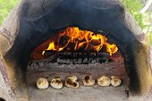 Stone wood oven with fire baking fresh homemade bread