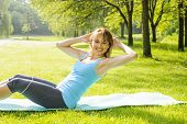 Female fitness instructor exercising doing sit-ups on yoga mat outside in green summer park