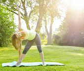 Female fitness instructor doing yoga extended triangle pose outdoors in morning sunshine