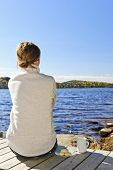 Woman sitting on dock relaxing by beautiful lake in Algonquin Park, Canada.