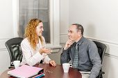 Female real estate agent talking to new home owner in office meeting room