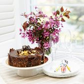Round gourmet chocolate cake on table next to window with plates, cutlery, and pink spring bouquet