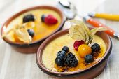 Sweet creme brulee desserts topped with fresh berries