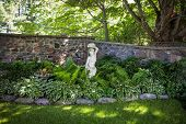Lush green summer garden with perennial plants and statue near stone wall