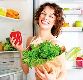 Healthy Eating Concept. Diet. Beautiful Young Woman near the Fridge  with healthy food. Fruits and V