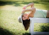 Beautiful Young Woman Lying On Bench In Park