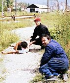 SARAJEVO, BOSNIA - JUNE 17: Two men duck for cover while trying to help another man critically injur