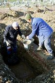 SARAJEVO, BOSNIA - DEC 12: Gravediggers bail water out of a frozen grave at cemetery on the grounds