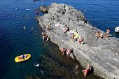 MANAROLA - ITALY: AUG 17: Bathers swim off the rocks in the marina of Manarola, Italy, on Sunday, Au