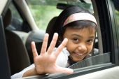 Little girl waving goodbye from a car