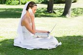 Side view of young bride using laptop and mobile phone while sitting on grass in park