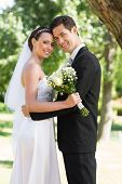 Portrait of happy newly wed couple with head to head standing in garden