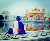 Vintage retro hipster style travel image of unidentifiable Seekh Nihang warrior meditating at Sikh t