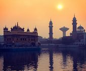 Vintage retro hipster style travel image of Sikh gurdwara Golden Temple (Harmandir Sahib) on sunrise. Amritsar, Punjab, India