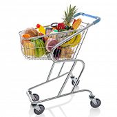 Shopping trolley full of fresh groceries isolated on a white background.