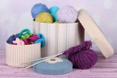 Decorative boxes with colorful skeins of thread on table on bright background