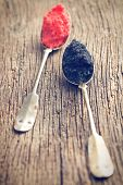 black and red caviar in spoon on wooden table
