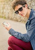 Teenager with sunglasses using a smart phone