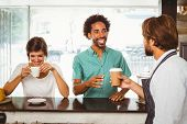 Barista serving two happy customers at the coffee shop