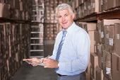 Smiling warehouse manager writing on clipboard in a large warehouse