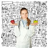 female doctor with green and red apples in her hands, and stethoscope on her neck