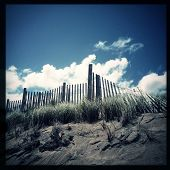 Instagram filtered image of sand dunes and an old wood fence