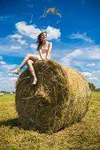 stock photo of windy weather  - Young woman sit on a newly built hay stack - JPG