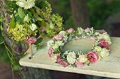 summer flower wreath on white wooden rustic swing in the garden